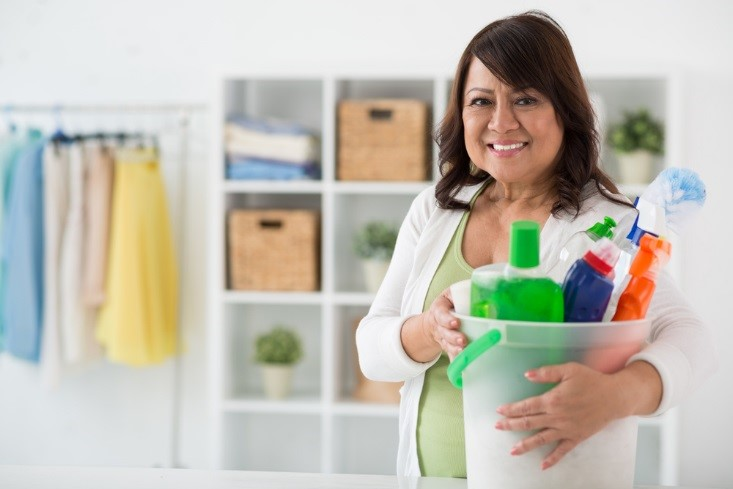 An executive housekeeper carrying cleaning supplies and smiling